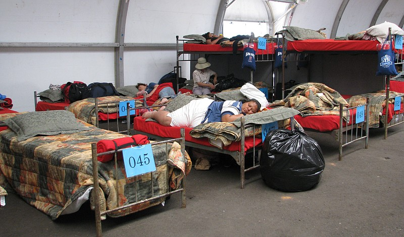 Dozens of homeless people lay on beds at the San Diego winter homeless shelte...