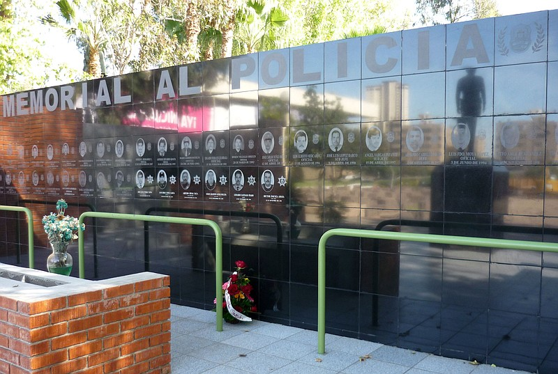 The names of fallen police officers are displayed on a memorial wall in Tijua...