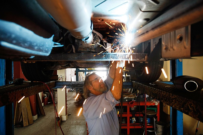Kevin Doyle from Mad Hatter Muffler shop works on replacing a catalytic conve...