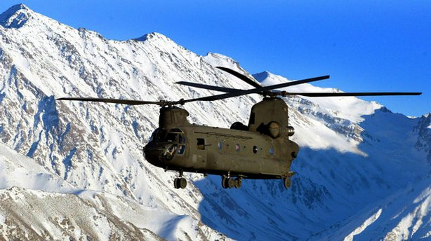A U.S. Army helicopter flies over the snow-capped Hindu Kush mountains of Afg...