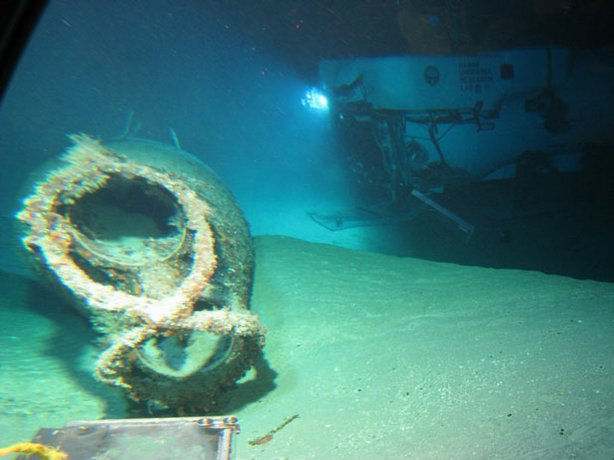 "Wreck site showing the bow section and the figure-eight neck cutter with empty torpedo tubes. The research vessel is in the background. NOVA joins an exclusive dive beneath the waters of Pearl Harbor to trace new clues to the historic sinking of the USS Arizona. The discovery of a Japanese ""midget sub"" far from the scene of the battle raises new questions about the Arizona's final hours."