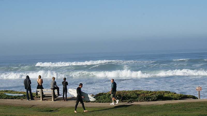 Bystanders gathered along the beach in Del Mar to watch the huge waves on Jan...