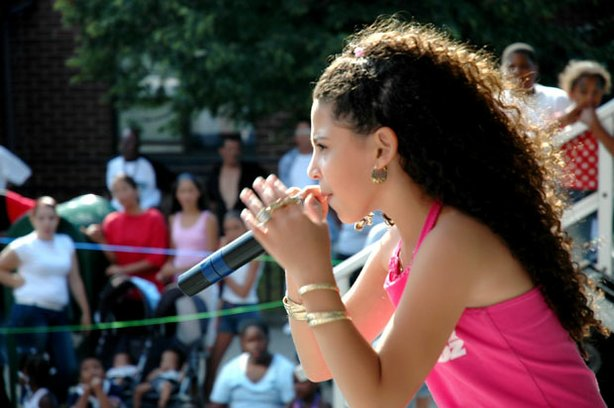 Young rapper P-Star (Priscilla Diaz ), age nine, performs at a Harlem street festival.
