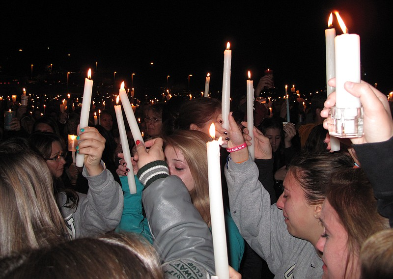 Mourners hold up candles in memory of 17-year-old Chelsea King during a vigil...