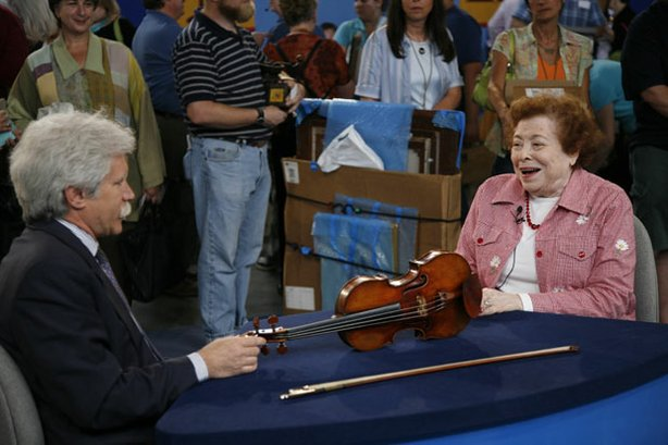 "At ""Antiques Roadshow"" in Baltimore, Maryland, this woman presents a violin and bow her husband acquired from a local violin shop in Washington, DC. Appraiser Fred Oster of Vintage Instruments, Inc. recognizes the instrument's unique construction and materials as the work of Nicolas Lupot. The accompanying bow is identified as a 19th-century piece by Dominique Peccatte, one of the most influential bow makers in history. Together, violin and bow make beautiful music to the tune of $140,000 and $20,000 respectively."
