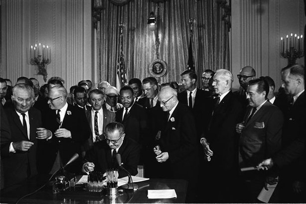 President Lyndon B. Johnson signs the 1964 Civil Rights Act as Martin Luther King, Jr.,and others look on, July 2, 1964.