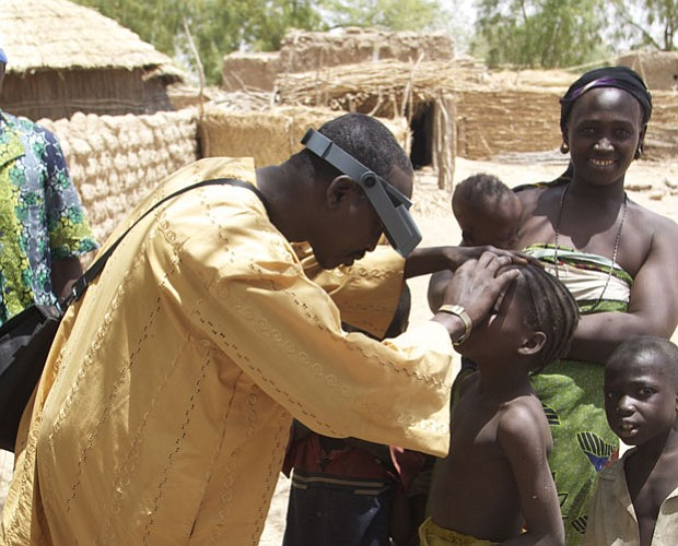 In a remote village of Niger, a doctor checks the eyes of children for signs ...