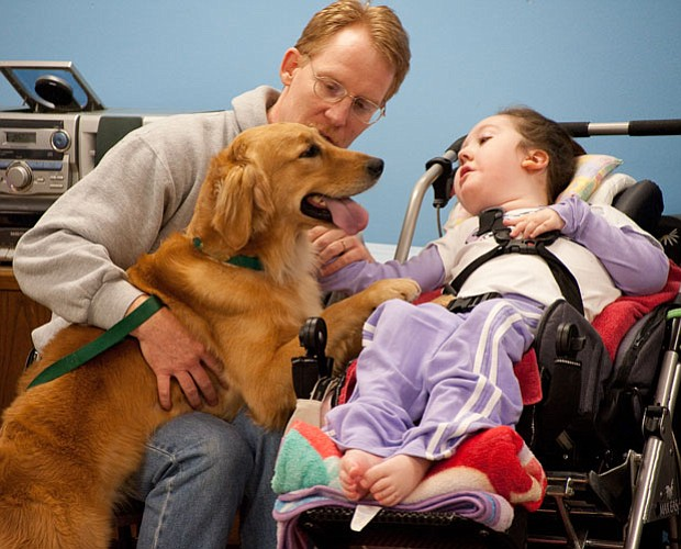 Julia's dad, Tom, helps her bond with her assistance dog, Thelma, during the ...