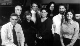 KPBS Newsroom in the 1990s set a new standard for radio journalism.  Pictured from left to right: Scott Horsley, Michael Marcotte, Alison St John, Erik Anderson, Carrie Kahn, Nancy Greenlease, Tom Fudge, and Christine Noriega.