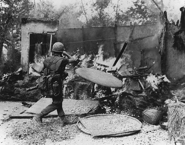 A soldier burning down a hut in My Lai village. Ron Haberle's photos of My La...
