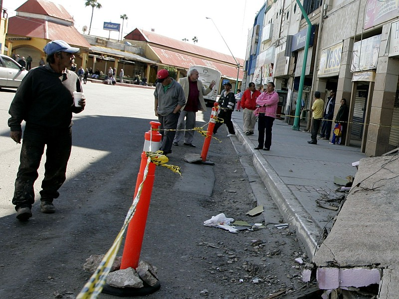 Residents survey the damage to a building after an earthquake April 5, 2010 i...