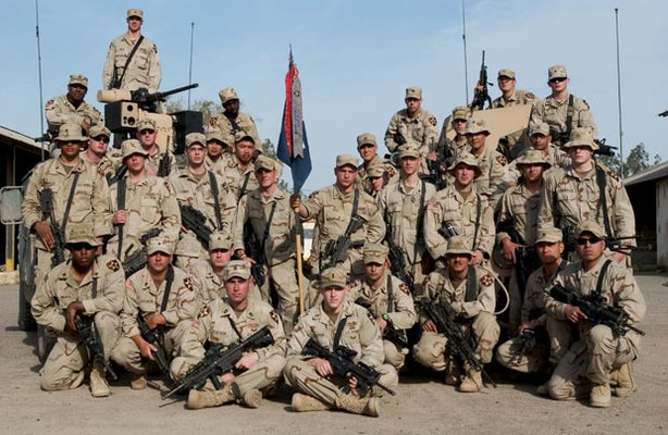 The soldiers of Third Platoon, Charlie Company, 1/506 Infantry Division pose at Camp Manhattan, Iraq, before heading out on patrol in 2005. David Nash (center, holding flag) was later thrown out of the army for failing a drug test. Four other members of the platoon were subsequently imprisoned for crimes committed in the United States.