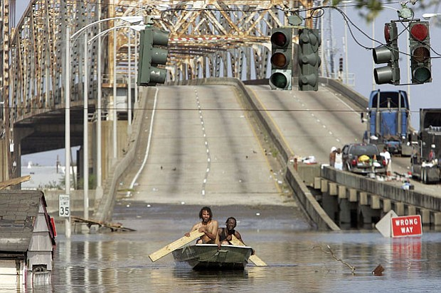 Two men paddle in high water after Hurricane Katrina devastated the area, Aug...