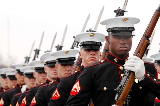 Marines in uniform standing at attention.