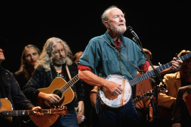 Folk music icon Pete Seeger plays the banjo and sings with Arlo Guthrie (back left) at the Woody Guthrie Tribute Concert at Severance Hall in Cleveland, September 1996.