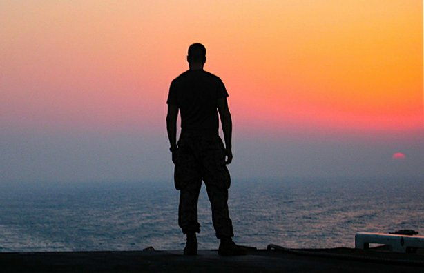 "A lone sailor stands facing the horizon aboard the ""USS Nimitz"" in the Persian Gulf, 2005."
