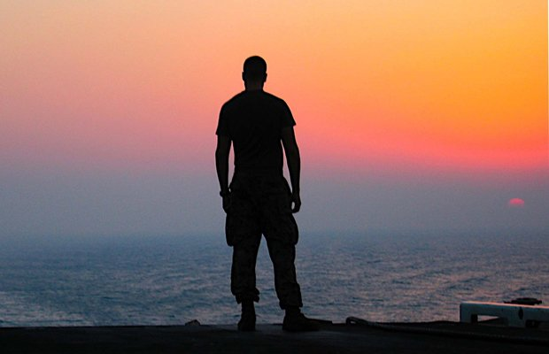 A lone sailor stands facing the horizon aboard the