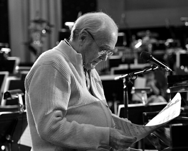 A black and white photo of composer Michel Legrand reading a sheet of music.