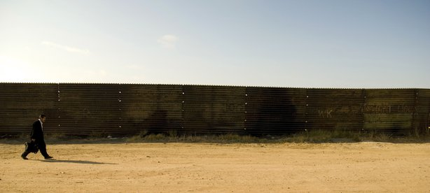 A man walks along a rusty segment of the fence on the Mexican side. Many migr...