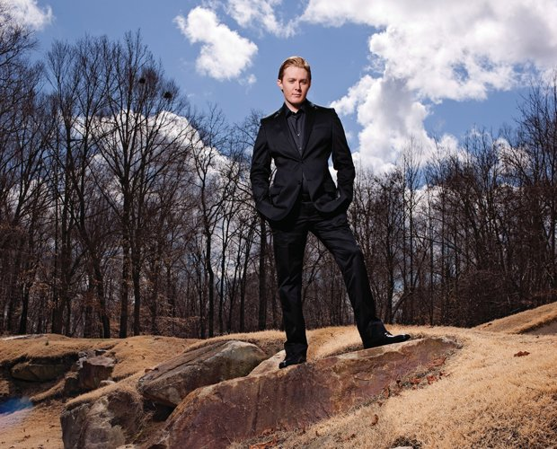 Promotional photo of Clay Aiken standing outdoors, dressed in a black suit. C...