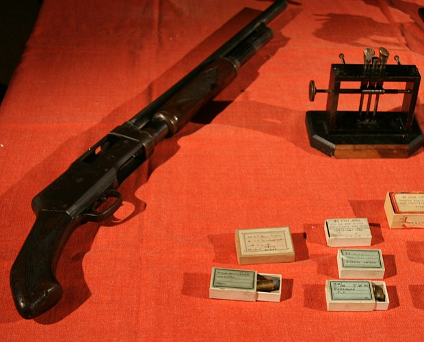 A table display with a 12-gauge shotgun and ballistics. The gun came to our c...