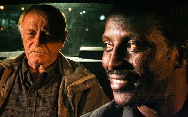 William (Red West) and Solo (Souléymane Sy Savané) in Solo's cab. Solo drives...