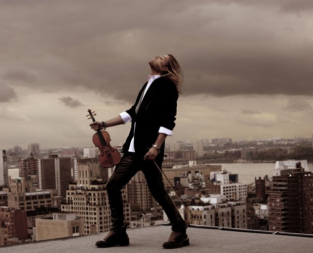 Promotional photo of musician David Garrett on a roof top with his violin.
