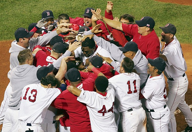 The Boston Red Sox' David Ortiz is mobbed by teammates after his game-and ser...