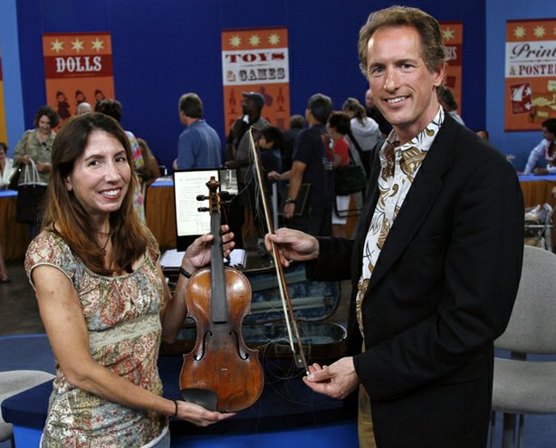 "In the third and final hour of ""Antiques Roadshow"" from Honolulu, Hawaii, appraiser David Bonsey of Skinner plucks the owner of this antique violin out of the crowd. The violin and bow were passed down to the owner by her great-aunt - a professional violinist who purchased the instrument in 1921. According to accompanying documentation, the violin is a rare Camilli, made in 1737 in Mantua, Italy. Upon further inspection, however, Bonsey reveals that it's a fine forgery. Despite this sour note, the violin and bow as a pair could still make beautiful music together with an auction estimate of at $12,000 - $16,000."