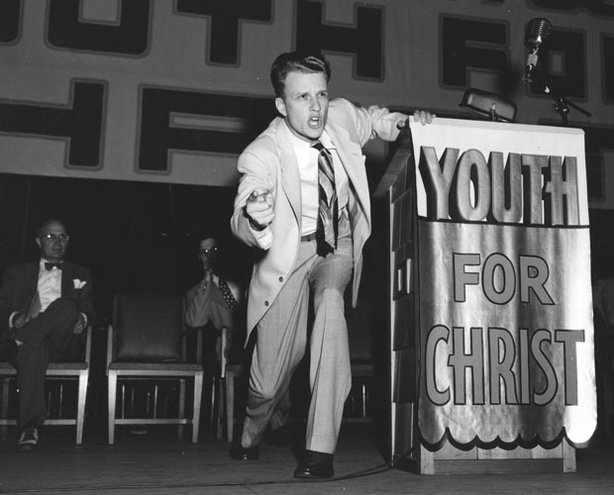 "Historical photo of Reverend Billy Graham on stage at a rally for ""Youth For Christ."" In 1947, at the age of 27, Reverend Billy Graham began traveling across America hoping to spark a spiritual revival with his own conversion story. Believing he could save America by saving souls, he became the country's most famous preacher of all time."