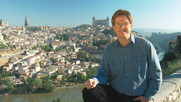Rick Steves with a scenic view of Toledo, Spain in the background.