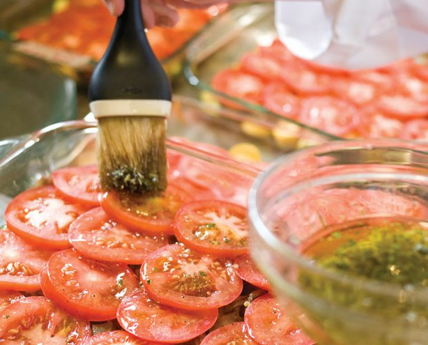 A pan of sliced tomatoes brushed with olive oil from AMERICA'S TEST KITCHEN. ...