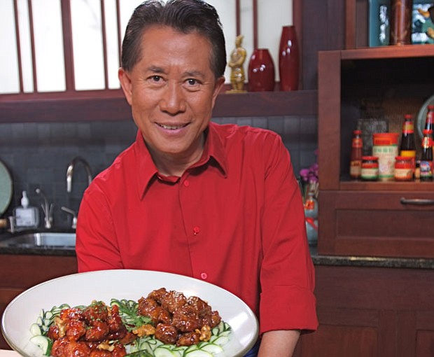 International chef and television host Martin Yan in the kitchen holding a pl...