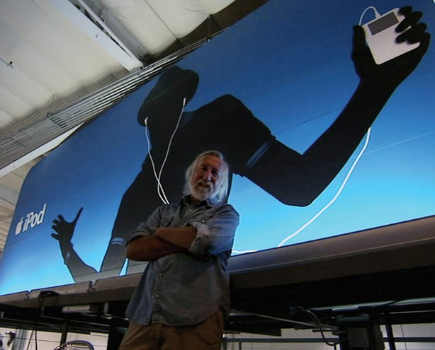 Lee Clow, surfer and chairman and chief creative officer of TBWA WorldwideChiatDay, in front of a full-size iPod billboard inside the Los Angeles office. Clow has been largely responsible for Apple's ad campaigns since 1984.