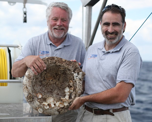 Craig Mullen and Timmy Gambin with a Roman mortar from 1st century BC, from