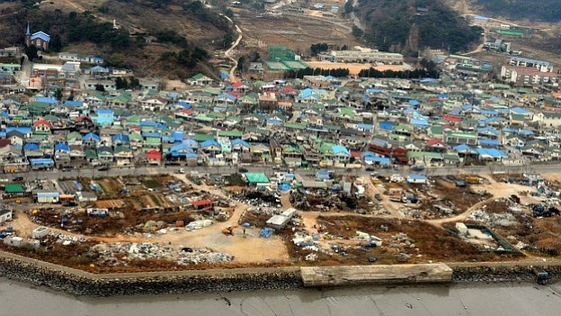 Destroyed houses are seen Wednesday on Yeonpyeong Island, South Korea, follow...
