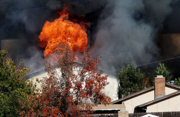 Flames engulf the rented home of George Jura Jakubec after it was set ablaze by officials December 9, 2010 in Escondido, California.