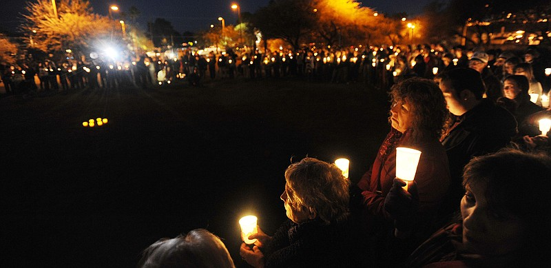 People gather for a vigil at University Medical Center for U.S. Rep. Gabriell...