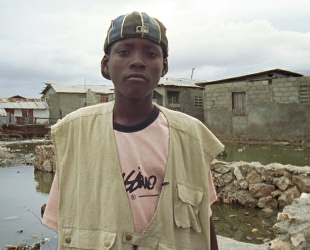"Denick, age 14, in his neighborhood, Haiti. ""Children of Haiti"" follows three teenage boys who reflect on their country and their lives, while sharing a common dream of education, government assistance, and social acceptance."