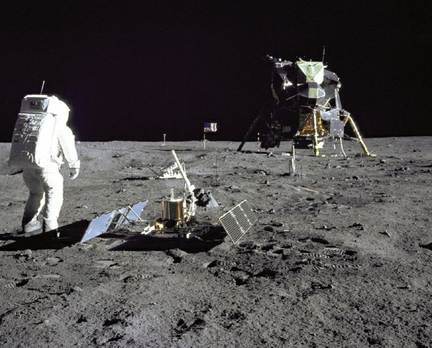 """Astronaut Edwin E.""""Buzz"""" Aldrin Jr., Lunar Module pilot, is photographed during the Apollo 11 extravehicular activity on the Moon. He has just deployed the Early Apollo Scientific Experiments Package (EASEP). In the foreground is the Passive Seismic Experiment Package (PSEP); beyond it is the Laser Ranging Retro-Reflector (LR-3); in the center background is the United States flag; in the left background is the black and white lunar surface television camera; in the far right background is the Lunar Module """"Eagle"""". Astronaut Neil A. Armstrong, commander, took this photograph with a 70mm lunar surface camera."""