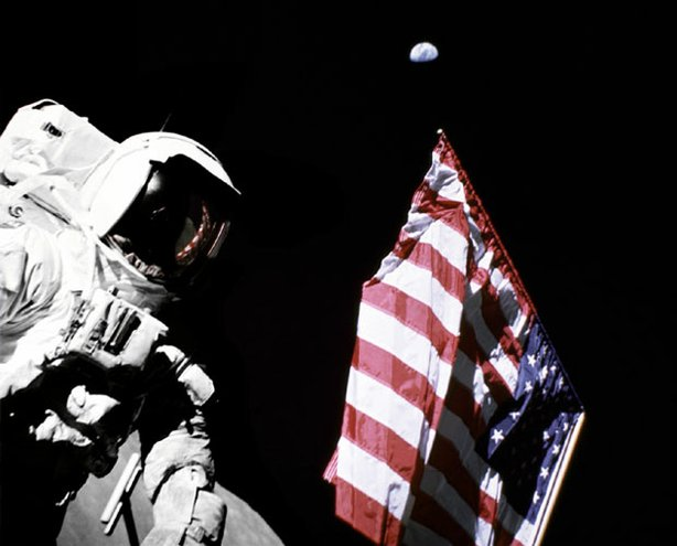 Geologist-Astronaut Harrison Schmitt, Apollo 17 Lunar Module pilot, is photographed next to the American Flag during extravehicular activity (EVA) of NASA's final lunar landing mission in the Apollo series. The photo was taken at the Taurus-Littrow landing site. The highest part of the flag appears to point toward our planet earth in the distant background.