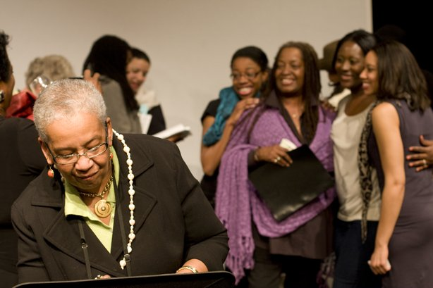 "Editor Barbara A. Seals Nevergold signs copies of her book ""Go, Tell Michelle"" while the actresses who performed in the staged reading of the book get their picture taken in the background."