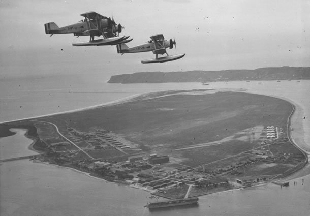 NAS North Island, San Diego, CA. View taken about 1926, showing Curtiss TS-2 floatplanes from VF-1 flying above USS Langley (CV 1).