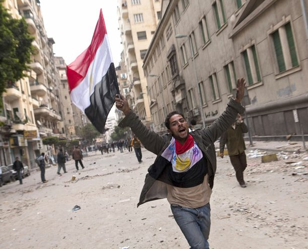 A man holding an Egyptian flag runs through the streets of Cairo. Anti-government protesters have called for Egyptian president Hosni Mubarak to step down.