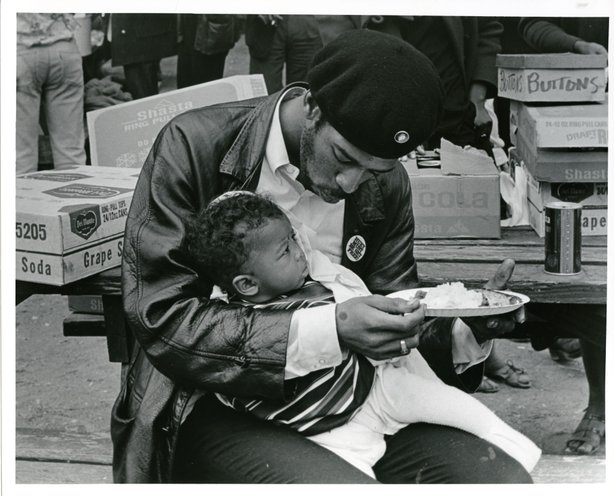 Black Panther feeding son at Free Huey rally, Oakland, 1968