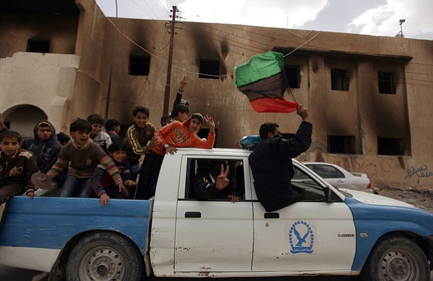 Members of Libya's police forces waving the country's old national flag and w...
