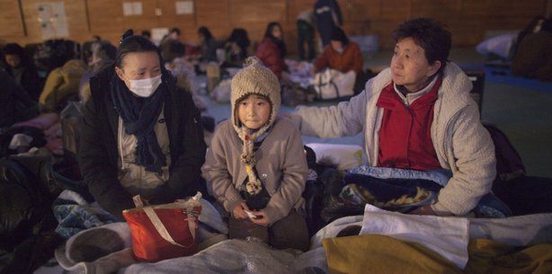 Yukie Ito, (L) tries to comfort her daughter Hana,8, (C) with grandmother Tamiyo (R) at a cold refugee center for the homeless March 16, 2011 in Kesennuma, Miyagi province, Japan.