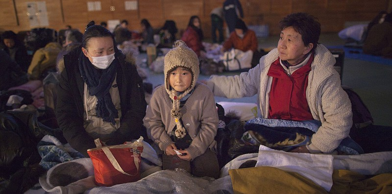 Yukie Ito, (L) tries to comfort her daughter Hana,8, (C) with grandmother Tam...