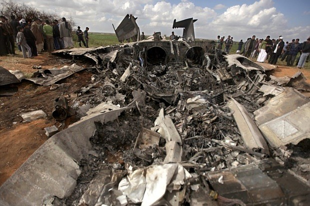 Libyans gather around a U.S. F-15 fighter jet after crashing while on a missi...