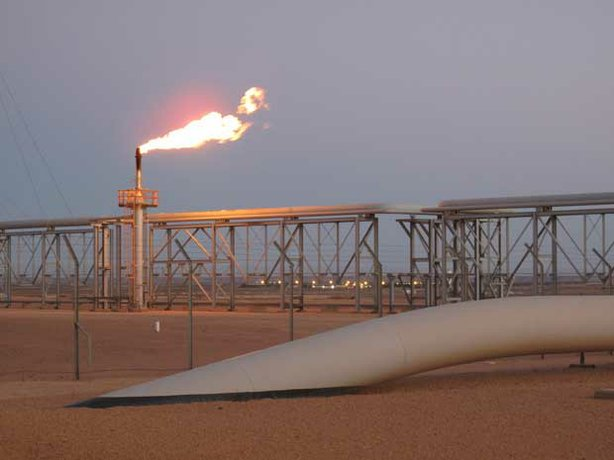 The sun sets over the large carbon dioxide pipeline that enters the ground in the middle of the Sahara desert at the In-Salah natural gas plant. This pipe is filled with carbon dioxide that is being pumped and stored deep underground.